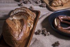 在木桌上的各种各样的新近地被烘烤的面包 免版税库存照片