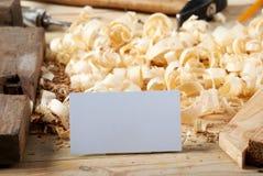 在木桌上的名片有锯木屑的木匠工具的 库存照片