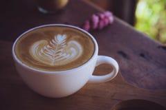 在木桌上的咖啡拿铁白色杯子在咖啡馆在早晨时间的咖啡店 免版税库存照片