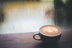 在木桌上的咖啡拿铁,下雨,外面 免版税库存照片