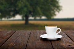 在木桌上的咖啡有美好的领域背景 免版税库存图片