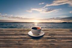 在木桌上的咖啡杯与旁边河 免版税库存图片