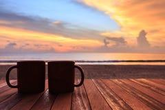 在木桌上的咖啡杯在日落或日出海滩 图库摄影