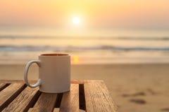 在木桌上的咖啡杯在日落或日出海滩 库存图片