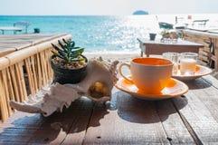 在木桌上的咖啡杯在beauti的海滩前面 图库摄影