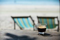 在木桌上的咖啡杯有海&沙子背景 库存图片