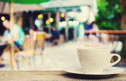 在木桌上的咖啡杯有迷离咖啡店背景 免版税库存图片