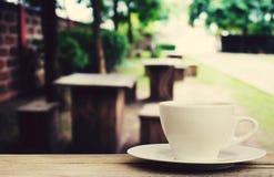 在木桌上的咖啡杯有迷离咖啡店背景 免版税库存照片