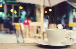在木桌上的咖啡杯有迷离咖啡店背景 库存图片