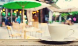 在木桌上的咖啡杯有迷离咖啡店背景 图库摄影
