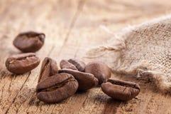 在木桌上的咖啡粒 免版税库存图片