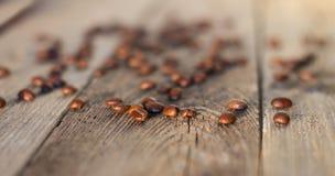 在木桌上的咖啡豆在日落发出光线 免版税库存图片