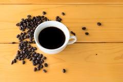 在木桌上的咖啡豆杯子 库存照片