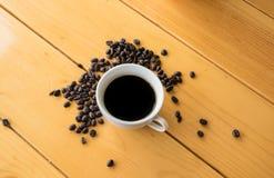 在木桌上的咖啡豆杯子 免版税库存照片