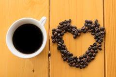 在木桌上的咖啡豆杯子 免版税图库摄影