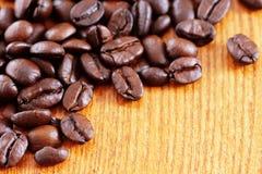 在木桌上的咖啡豆 免版税库存图片