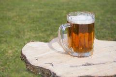 在木桌上的唯一啤酒杯特写镜头 图库摄影