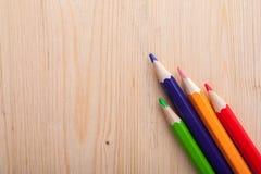 在木桌上的四支五颜六色的铅笔 图库摄影