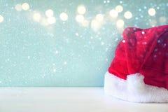 在木桌上的圣诞老人红色帽子 闪烁覆盖物 库存照片
