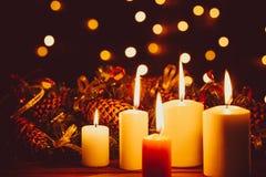 在木桌上的圣诞节灼烧的蜡烛在光亮诗歌选bokeh背景在晚上 免版税库存照片