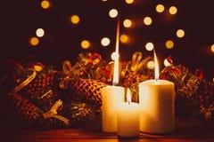 在木桌上的圣诞节灼烧的蜡烛在光亮诗歌选bokeh背景在晚上 库存图片