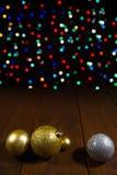 在木桌上的圣诞节球在五颜六色的bokeh背景 免版税库存图片