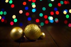 在木桌上的圣诞节球在五颜六色的bokeh背景 库存图片