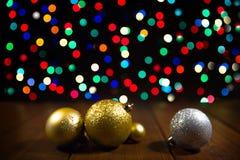 在木桌上的圣诞节球在五颜六色的bokeh背景 库存照片