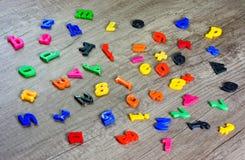 在木桌上的塑料信件字母表图象 免版税库存照片