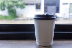 在木桌上的外带的咖啡杯 免版税库存图片