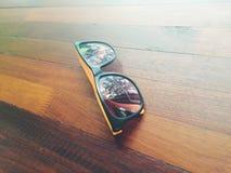 在木桌上的太阳镜 图库摄影