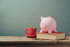 在木桌上的存钱罐与咖啡杯和书 银行票据贪心放置的节省额 免版税库存照片