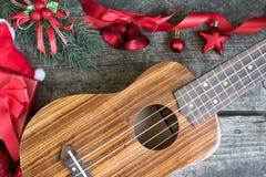 在木桌上的尤克里里琴与红色圣诞节装饰品 免版税库存照片
