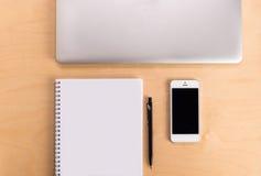 在木桌上的工作区与膝上型计算机、写生簿、铅笔和电话 设计师的工作办公桌的创造性的概念 库存图片