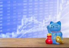 在木桌上的幸运的猫银行有迷离股市背景 免版税库存图片