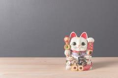 在木桌上的幸运的猫 免版税库存图片