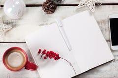 在木桌上的开放笔记本与电话 免版税库存照片