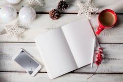 在木桌上的开放笔记本与电话 库存图片