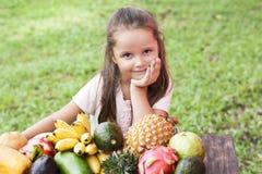 在木桌上的异乎寻常的果子 与笑愉快的女孩的夏天背景 库存图片