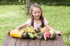 在木桌上的异乎寻常的果子 与笑愉快的女孩的夏天背景 库存照片