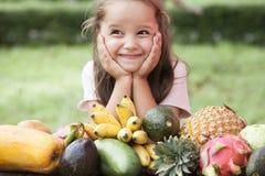 在木桌上的异乎寻常的果子 与笑愉快的女孩的夏天背景 免版税库存图片