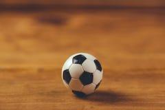 在木桌上的微型塑料足球 免版税库存照片