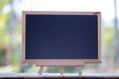 在木桌上的微型空白的黑板与拷贝空间 黑板 图库摄影