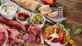 在木桌上的意大利开胃小菜 免版税库存照片