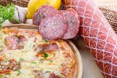 在木桌上的意大利薄饼 真实的热的鲜美薄饼用蒜味咸腊肠, 库存照片