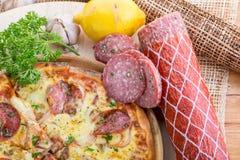 在木桌上的意大利薄饼 真实的热的鲜美薄饼用蒜味咸腊肠, 免版税库存图片