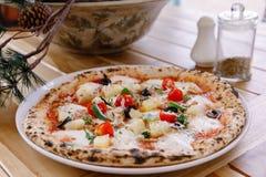 在木桌上的意大利鲜美薄饼 免版税图库摄影