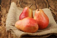 在木桌上的成熟水多的有机红色梨 免版税库存照片