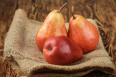 在木桌上的成熟水多的有机红色梨 免版税图库摄影