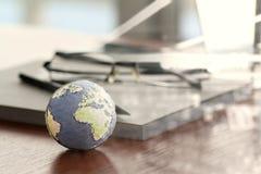 在木桌上的手拉的纹理地球在笔记本附近 图库摄影